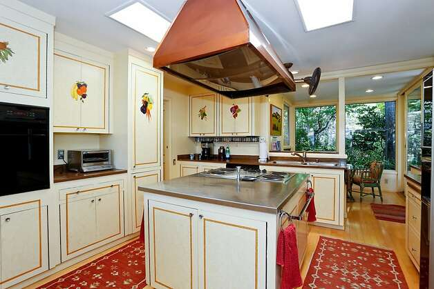 The kitchen features cabinets hand-painted in the French Country style. Photo: Frank Howard Allen Realty