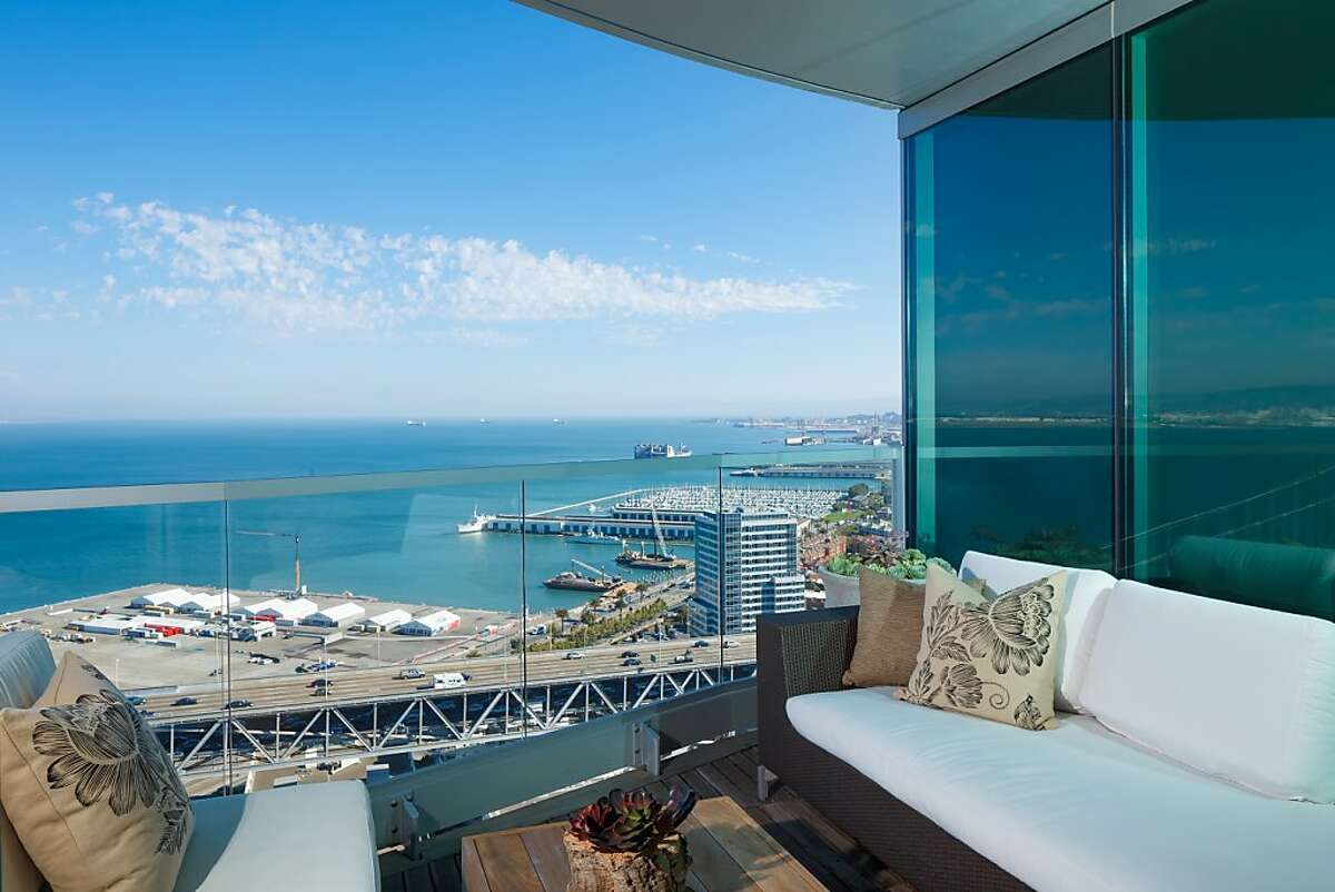 Panoramic views from the upper-level guest deck, the home's second terrace buffered by a half-wall of glass, extend outward with the Pacific Ocean.