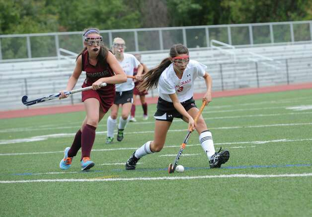 Pomperaug High School's #6, Alyssa Vagnini fights with Greenwich High School's #3, Sydney Cole, in a game of field hockey in Greenwich, Monday, Oct. 8, 2012. Greenwich won 5 to 1. Photo: Helen Neafsey / Greenwich Time