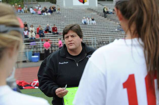 Greenwich High School field hockey coach Ally Orrico speaks with the team at the game with Pomperaug High School and Greenwich Monday, Oct. 8, 2012. Photo: Helen Neafsey / Greenwich Time