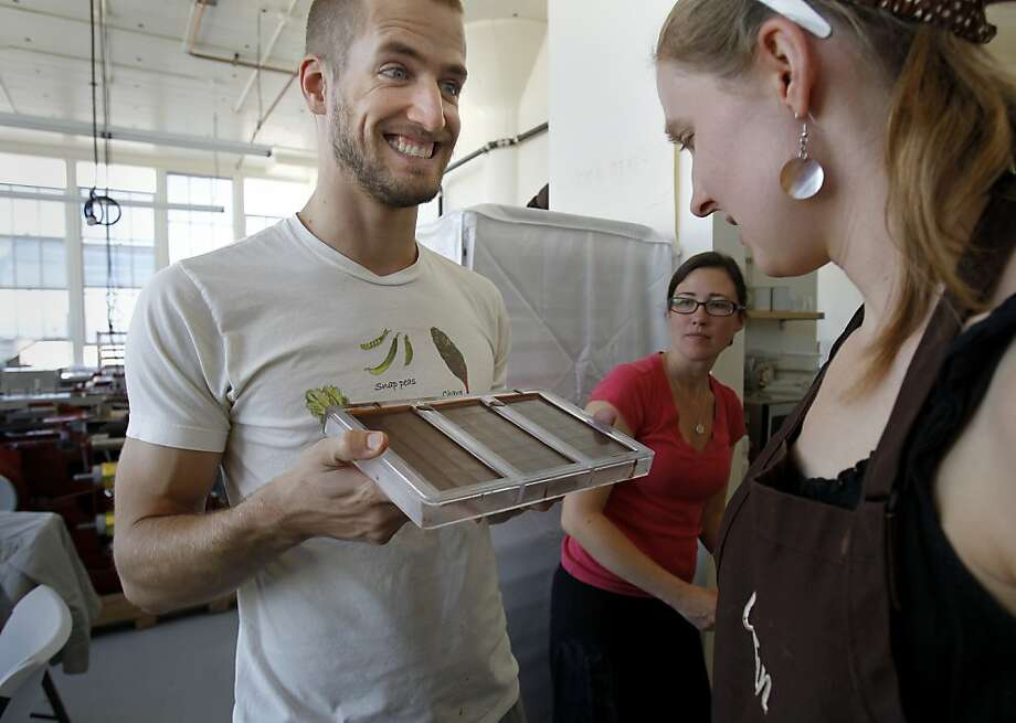 Dandelion chocolatier Tod Chubrich (left) shows some finished bars to Caitlin Lacey (right). Photo: Brant Ward, The Chronicle