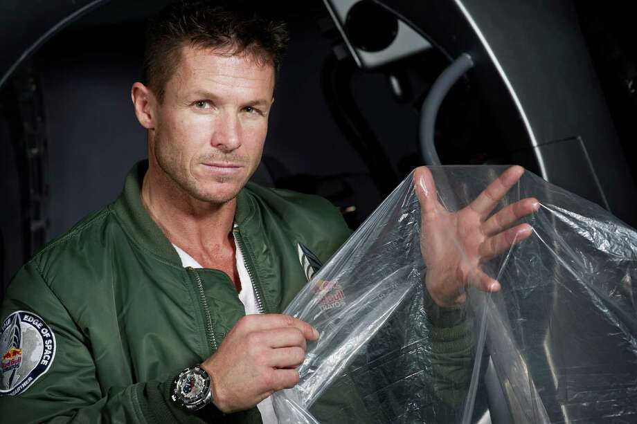 """In this Feb. 23, 2012 photo provided by Red Bull Stratos, pilot Felix Buamgartner of Austria shows a piece of the balloon material during the Red Bull Stratos egress training in Lancaster, Calif. It's described as a """"40-acre dry cleaner bag,"""" that, when first filled, will stretch 55 stories high. On Monday, this special ultra-thin helium balloon is scheduled to liftoff from Roswell, N.M., to carry """"Fearless Felix"""" Baumgartner 23 miles into the stratosphere for what he hopes will be a history-making, sound barrier-breaking skydive. (AP Photo/Red Bull Stratos, Joerg Mitter) Photo: Joerg Mitter, Associated Press / Red Bull Stratos"""
