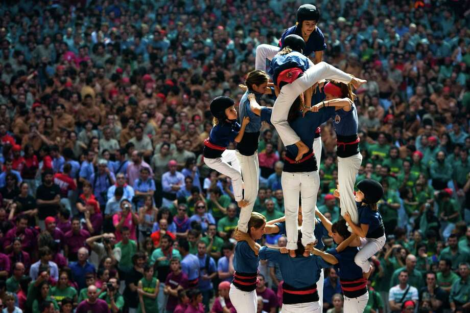 Members of the Colla 'Caprogossos de Mataro' climb up as they construct a human tower during the 24th Tarragona Castells Competition on October 7, 2012 in Tarragona, Spain. The 'Castellers' who build the human towers with precise techniques 