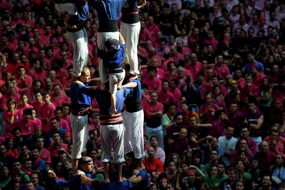A young member of the Colla 'Vila de Gracia' climbs up as they construct a human tower during the 24th Tarragona Castells Competition on October 7, 2012 in Tarragona, Spain. Photo: David Ramos, Getty Images / 2012 Getty Images