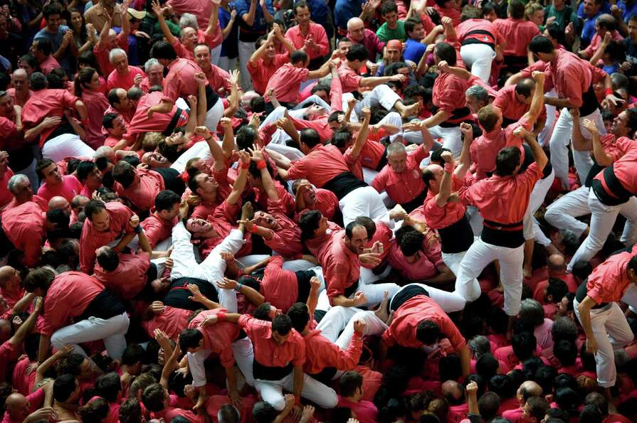 Members of the Colla 'Vella de Valls' celebrate after building a human tower during the 24th Tarrago
