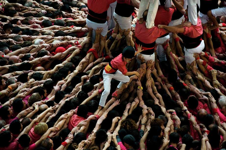 A young member of the Colla 'Vella de Valls' descends after bulding a human tower during the 24th Tarragona Castells Competition on October 7, 2012 in Tarragona, Spain. Photo: David Ramos, Getty Images / 2012 Getty Images