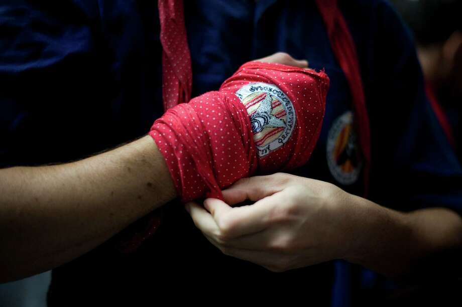A  member of the Colla 'Capgrossos de Mataro' ties a headscarf roung his wrist during the 24th Tarragona Castells Competition on October 7, 2012 in Tarragona, Spain.  Photo: David Ramos, Getty Images / 2012 Getty Images