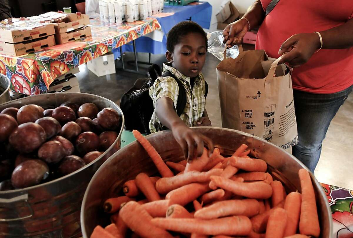 Kenyon Tate, 6, helps his mother gathers fruits and vegetables during the free weekly food distribution at the Mosaica Family Apartments in San Francisco, Calif., on Thursday October 4, 2012. The San Francisco and Marin Food Banks have for a second year in a row have been shorted $200,000 in federal funding, meaning nearly a half-million meals will go unserved next year unless new money shows up.