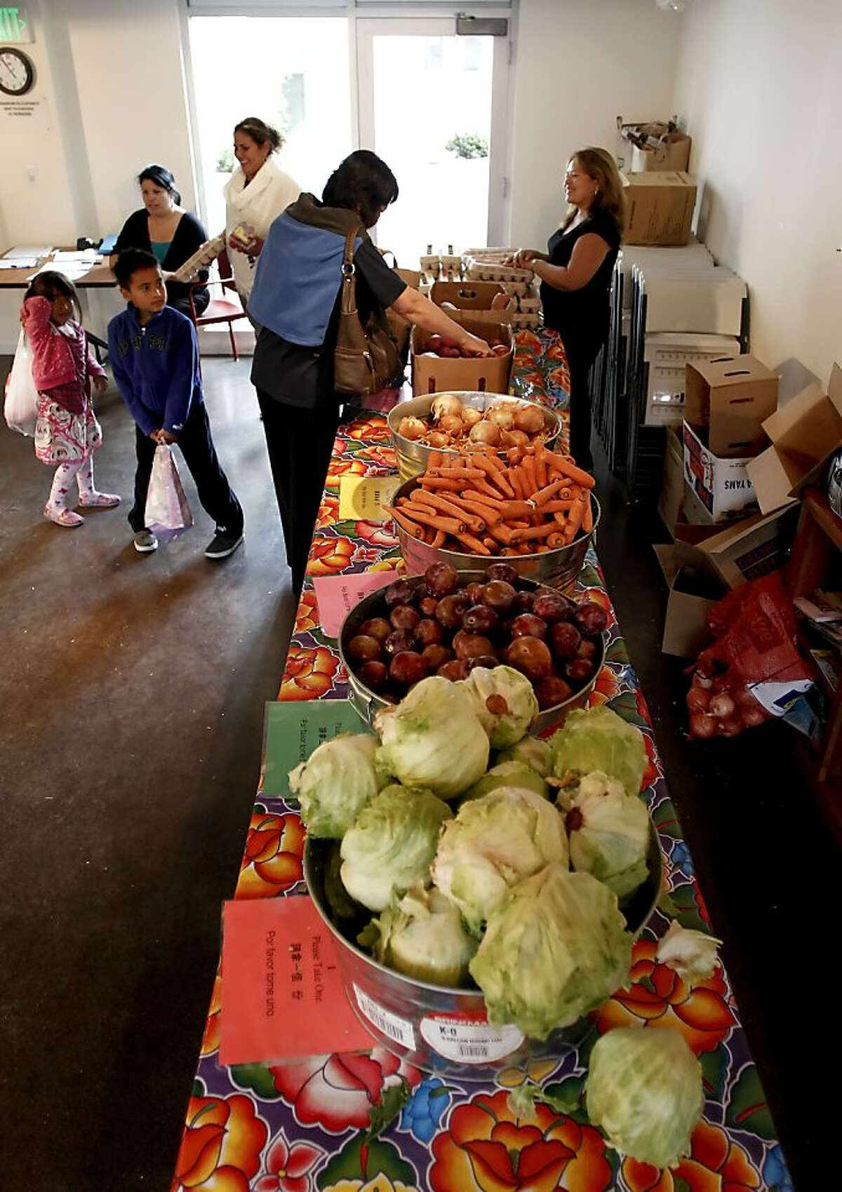 Residents gather bags of food during the free weekly distribution at the Mosaica Family Apartments in San Francisco, Calif., on Thursday October 4, 2012. The San Francisco and Marin Food Banks have for a second year in a row have been shorted $200,000 in federal funding, meaning nearly a half-million meals will go unserved next year unless new money shows up.