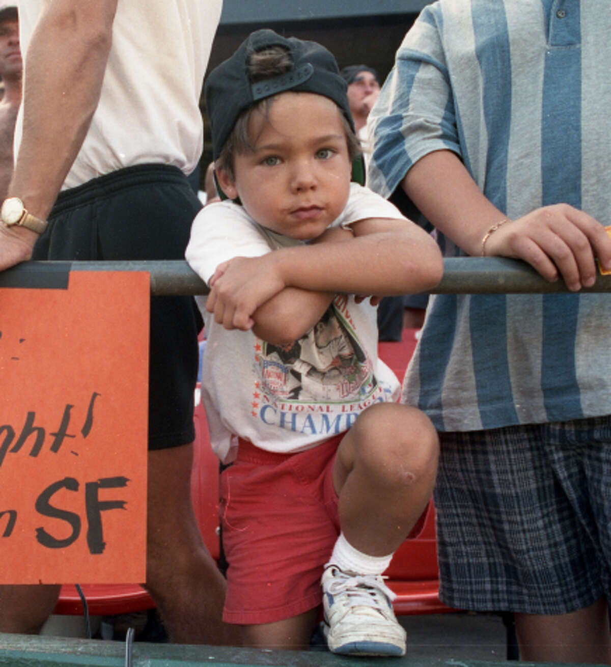 A young Brandon Crawford stands next to his father, Mike, while he holds a sign with a message for National League President Bill White on Sunday, Sept. 27, 1992, at Candlestick Park.