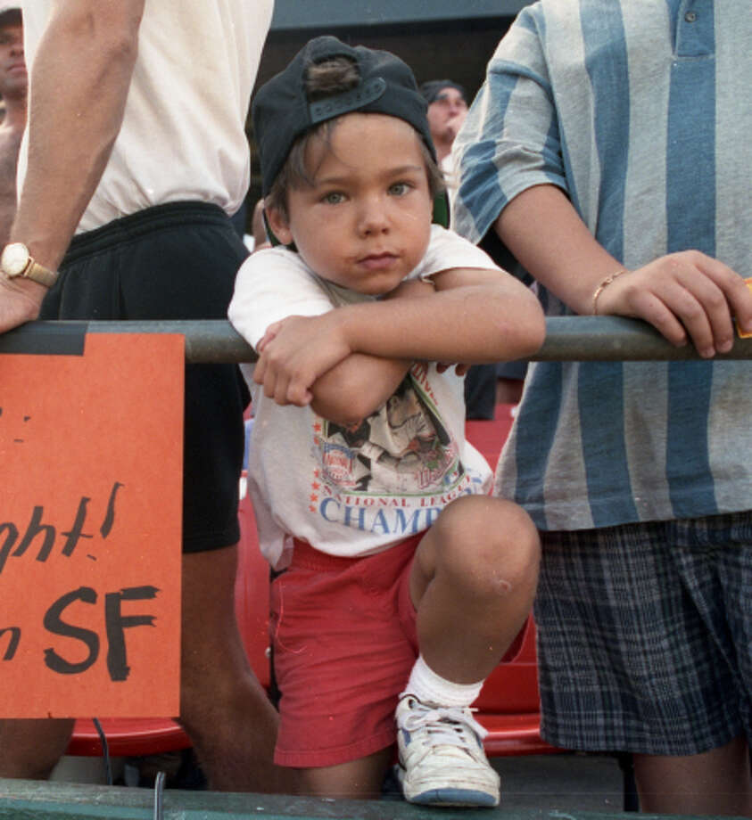 A young Brandon Crawford stands next to his father, Mike, while he holds a sign with a message for National League President Bill White on Sunday, Sept. 27, 1992, at Candlestick Park. Photo: Tom Levy / The Chronicle / ONLINE_YES