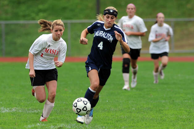 Lauralton Hall's Maggie Salandra moves the ball in front of Masuk's Jamie Madden during a high school soccer game in Monroe, Conn. Oct. 8th, 2012. Photo: Ned Gerard / Connecticut Post