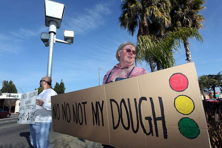 Roger Jones (right) and Howard Mora stand under a red-light camera as they protest the devices in Fremont in February. Photo: Lance Iversen, The Chronicle