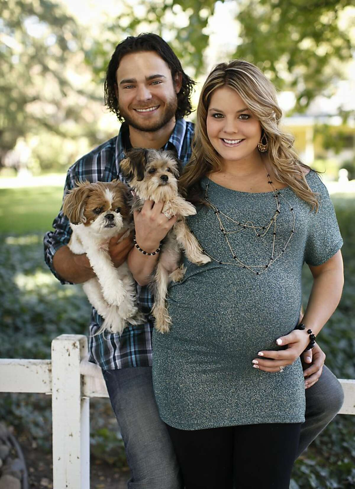 San Francisco Giants' shortstop Brandon Crawford and his wife, Jaylynne, seen with their dogs Marley, left, and Koda on Thursday, Oct. 4, 2012 near the home they are staying in in Walnut Creek, Calif., are expecting their first child in December.