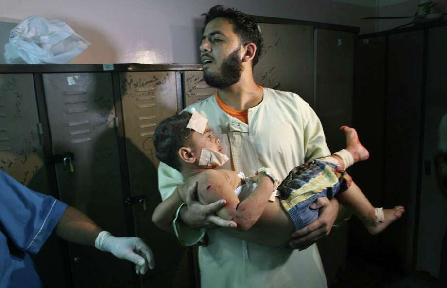 A Palestinian carries a wounded boy in a hospital following an Israeli airstrike in Rafah, Gaza Strip, on Sunday. Israel and militants were still battling Monday. Photo: Eyad Baba / AP