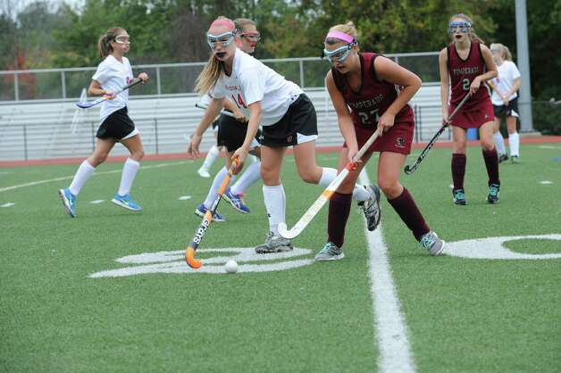 Greenwich High School's # 14, Anne Dunster fights with Pomperaug High School's #27, Amanda Silk in a game of field hockey in Greenwich, Monday, Oct. 8, 2012. Greenwich won 5 to 1. Photo: Helen Neafsey / Greenwich Time