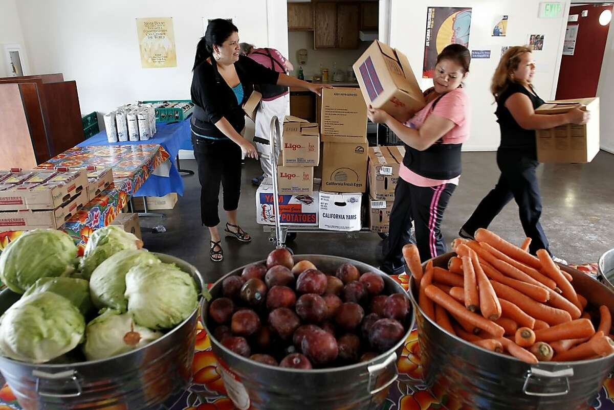 Tina Gonzales, (left to right), program coordinator, Edwin Drummond, volunteer, Magdelena Rojas, volunteer and Ana Servellon, case manager, unload boxes of food as they set up for the free weekly food distribution at the Mosaica Family Apartments in San Francisco, Calif., on Thursday October 4, 2012. The San Francisco and Marin Food Banks have for a second year in a row have been shorted $200,000 in federal funding, meaning nearly a half-million meals will go unserved next year unless new money shows up.