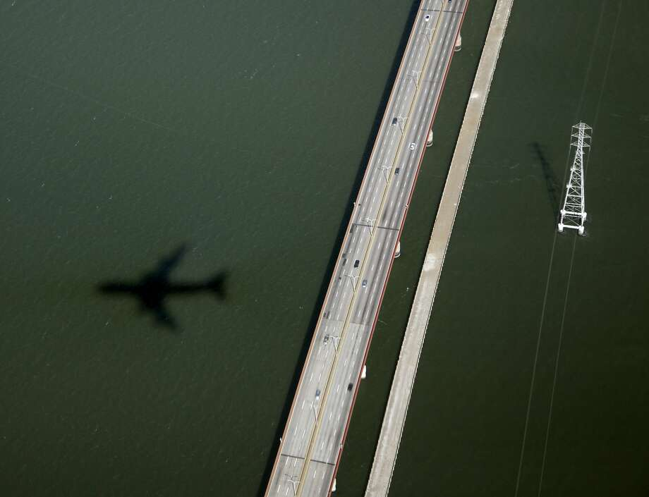 The shadow of Air Force One with President Barack Obama aboard is seen as it flies over the San Mateo Bridge and San Francisco Bay en rout to the San Francisco International Airport , Monday, Oct. 8, 2012, in San Francisco. (AP Photo/Carolyn Kaster) Photo: Carolyn Kaster, Associated Press