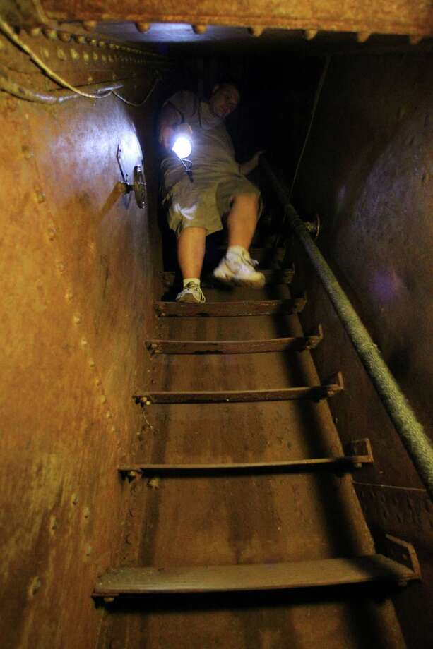 "Battleship Texas, Overnight Education Program Manager Paul McCann climbs down a stairway to an engine Boiler Room in an area visited during the Battleship Texas ""Hard Hat Tour"" Friday, Oct. 5, 2012, in La Porte. Photo: James Nielsen, Chronicle / © Houston Chronicle 2012"