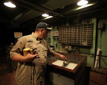 """Battleship Texas, Overnight Education Program Manager Paul McCann points to the plotting table in the Main Battery Plot in an area visited during the Battleship Texas """"Hard Hat Tour"""" Friday, Oct. 5, 2012, in La Porte. Photo: James Nielsen, Chronicle / © Houston Chronicle 2012"""