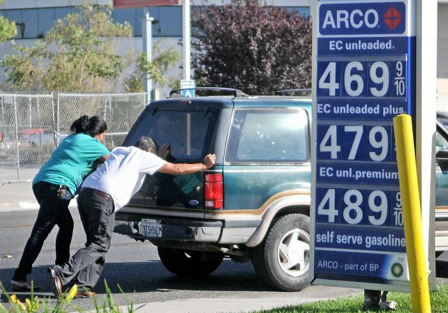 In Victorville, two people push an SUV into an Arco station after it ran out of gas nearby. Photo: David Pardo, Associated Press