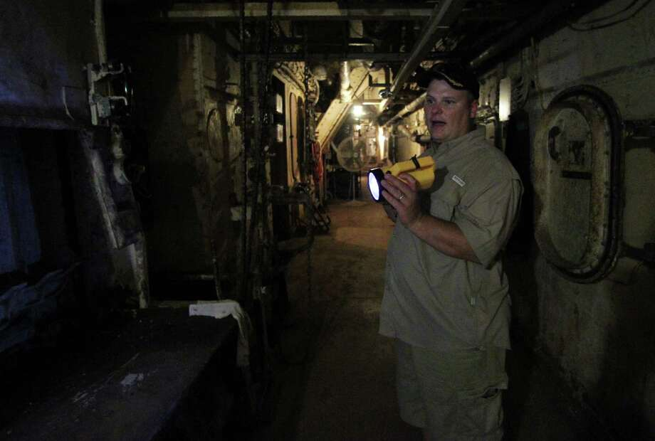 "Battleship Texas, Overnight Education Program Manager Paul McCann shines a flashlight in an area visited during the Battleship Texas ""Hard Hat Tour"" Friday, Oct. 5, 2012, in La Porte. Photo: James Nielsen, Chronicle / © Houston Chronicle 2012"