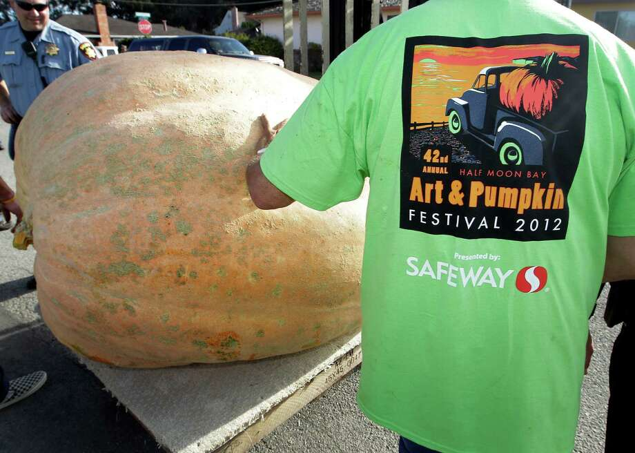 Workers push a giant pumpkin to be weighed at the Half Moon Bay Pumpkin Festival Weigh-off contest in Half Moon Bay, Calif., Monday, Oct. 8, 2012. Thad Starr from Pleasant Hill, Ore., won with a contest record of 1,775 pounds, making it a new California record. Starr wins six dollars for each pound, which equals $10,650. (AP Photo/Tony Avelar) Photo: Tony Avelar, Associated Press / FR155217 AP