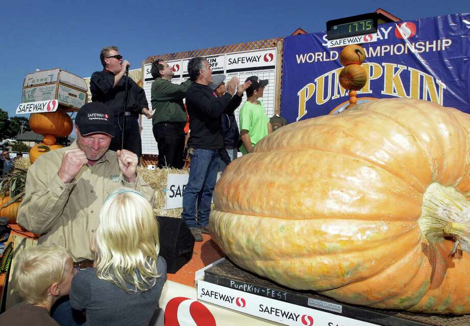 Thad Starr from Pleasant Hill, Ore. celebrates with his children Danika, 9, and Derek, 7, after winning the Half Moon Bay Pumpkin Festival Weigh-off contest in Half Moon Bay, Calif., Monday, Oct. 8, 2012. The pumpkin weighed 1,775 pounds, making it a new California record. Starr wins six dollars for each pound, which equals $10,650. (AP Photo/Tony Avelar) Photo: Tony Avelar, Associated Press / FR155217 AP