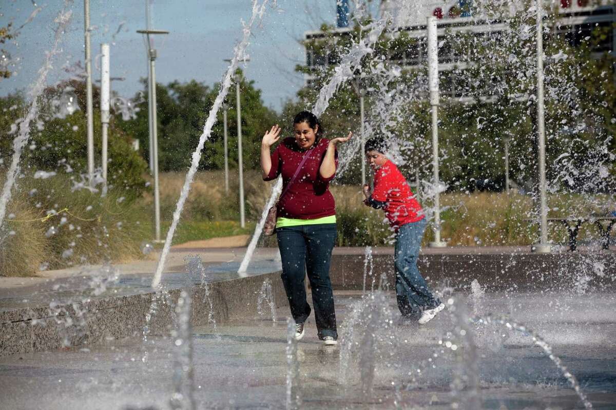 Jennifer Moreno, 20, and her brother Nicholas, 11, play in the Discovery Green fountain Monday. One developer believes it was the park that got the area going.