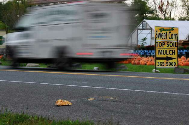 Traffic passes by pumpkin remnants on River Road in front of Gold Krest Farms on Monday Oct. 8, 2012 in East Greenbush, NY.  Three people were arrested after taking pumpkins from the farms, setting them up as a barricade in the road and watching someone crash into it.     (Philip Kamrass /  Times Union) Photo: Philip Kamrass / 10019576A