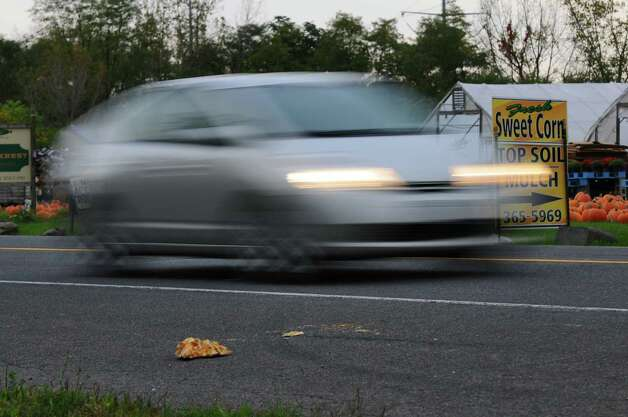 Traffic passes by pumpkin remnants on River Road in front of Gold Krest Farms on Monday Oct. 8, 2012 in East Greenbush, NY.  Three people were arrested after taking pumpkins from the farms, setting them up as a barricade in the road and watching someone crash into it.     (Philip Kamrass /  Times Union) Photo: Philip Kamrass / 00019576A