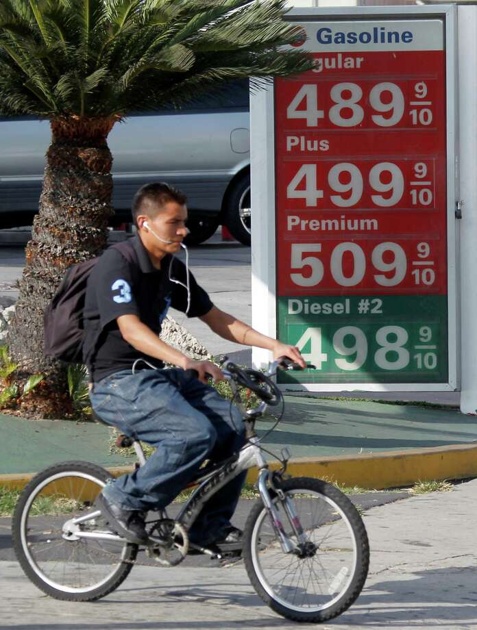 A bicyclist passes a sign showing gasoline prices topping the $5.00 mark at a 76 station in the Pico-Union neighborhood of downtown Los Angeles Friday, Oct. 5, 2012. (AP Photo/Reed Saxon) Photo: Reed Saxon / AP