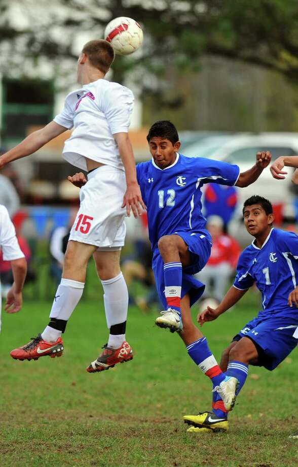 Ichabod Crane's Heriberto Gomez, center, battles Maple Hill's Kyle Hall, left, during their 5-0 victory over Maple Hill on Monday Oct. 8, 2012 in Schodack, NY.  (Philip Kamrass /  Times Union) Photo: Philip Kamrass / 00019563A