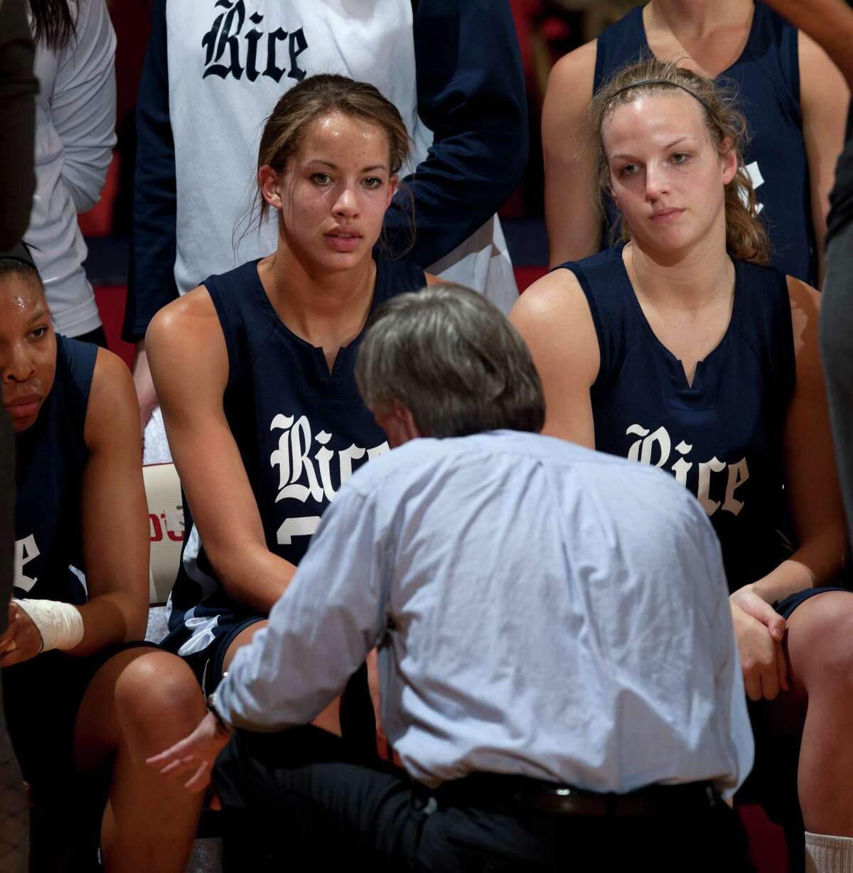 Rice's Jessica Kuster, center, listens in on head coach Greg Williams during a timeout.