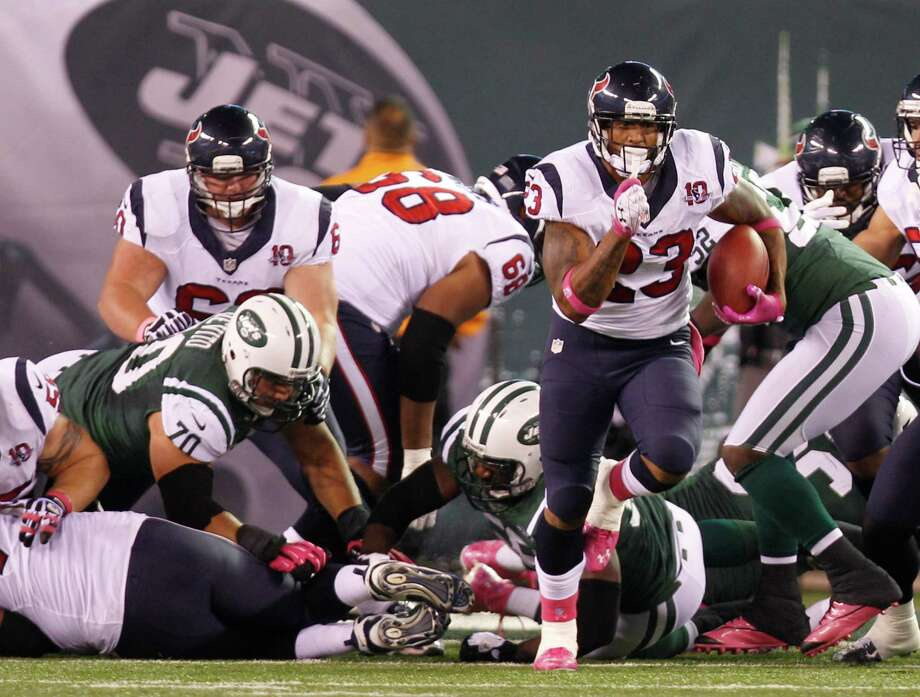 Houston Texans running back Arian Foster (23) breaks free of the New York Jets defense during the first quarter of a Monday Night Football game at MetLife Stadium on Monday, Oct. 8, 2012, in East Rutherford, N.J. Photo: Brett Coomer, Houston Chronicle / © 2012  Houston Chronicle