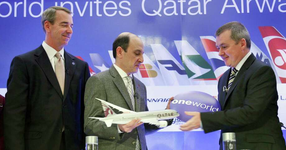 CEO of Qatar Airways Akbar Al Baker,  center, exchanges a gift with International Airlines Group chief executive Willie Walsh, right, while American Airlines CEO Tom Horton looks on during a news conference in New York, Monday, Oct. 8, 2012. Qatar Airways is joining an alliance of airlines including American Airlines, British Airways and nine other carriers that coordinate routes and allow passengers to earn frequent flier miles on each other's flights. (AP Photo/Seth Wenig) Photo: Seth Wenig / AP