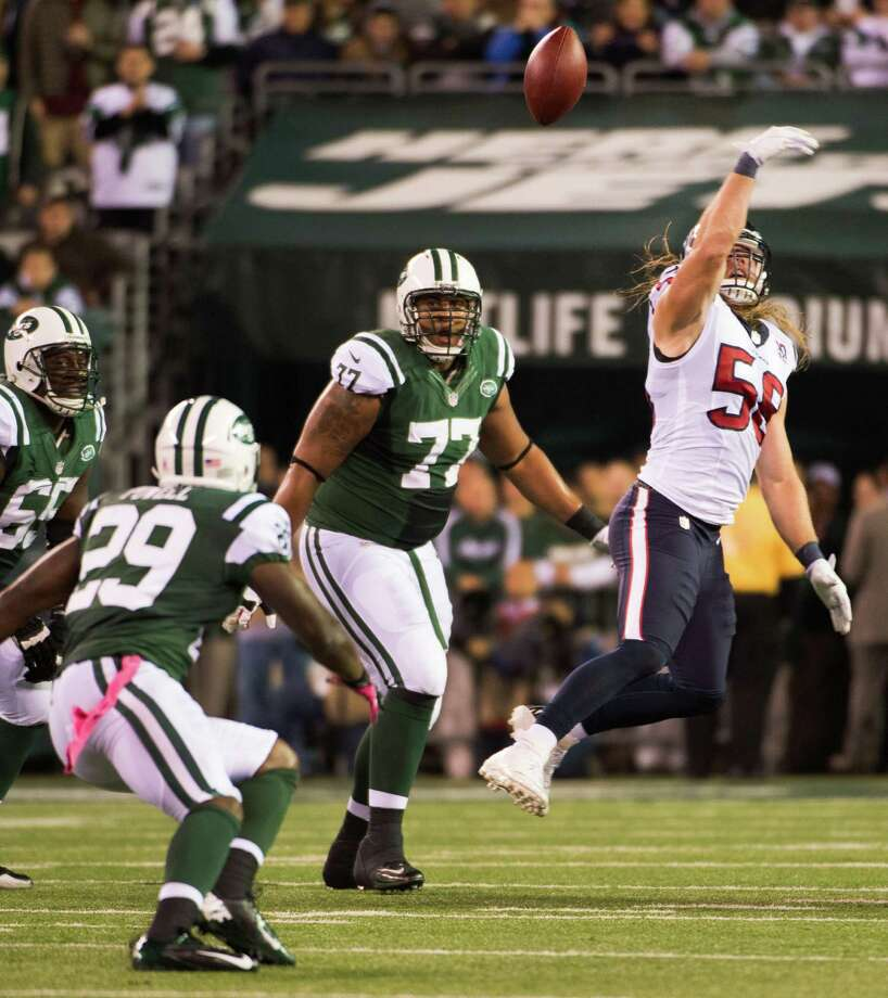 Houston Texans outside linebacker Brooks Reed (58) reaches for a tipped pass intended for New York Jets running back Bilal Powell (29) during the second quarter of a Monday Night Football game at MetLife Stadium on Monday, Oct. 8, 2012, in East Rutherford. Photo: Smiley N. Pool, Houston Chronicle / © 2012  Houston Chronicle