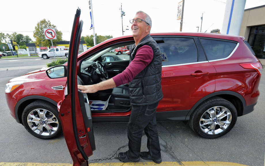 Paul Plaganis of Rensselaer gets into his new 2013 Ford Escape he just purchased at Orange Motors on Central Ave. Monday, Oct. 8, 2012 in Albany, N.Y. (Lori Van Buren / Times Union) Photo: Lori Van Buren