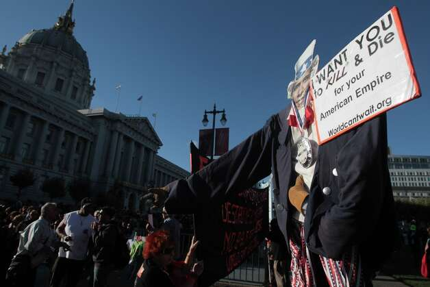 War protesters stand with an effigy of President Barack Obama as supporters of the President wait in line to attend a campaign event in San Francisco on Monday, Oct. 8, 2012. (AP Photo/Mathew Sumner) Photo: Mathew Sumner, Associated Press / FR170005 AP