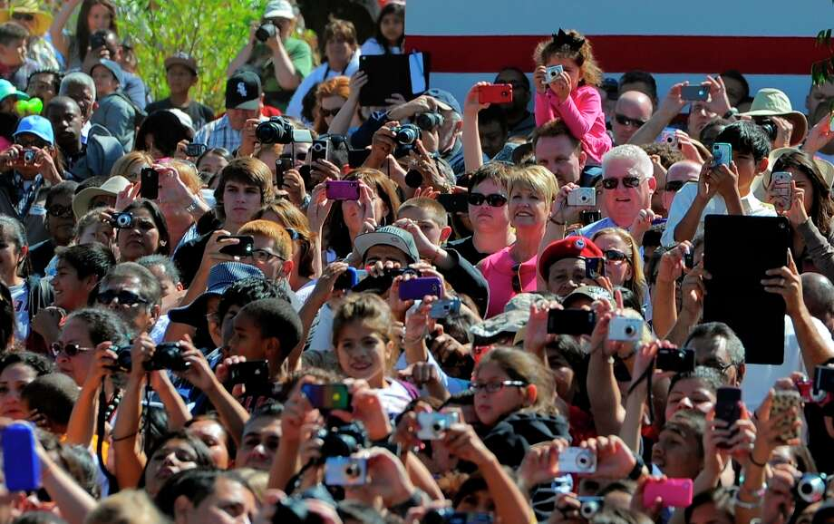 Supporters take pictures of President Barack Obama as he announces the establishment of the Cesar E. Chavez National Monument, Monday, Oct. 8, 2012, in Keene, Calif. The property is recognized worldwide for its historic link to civil rights icon Cesar  Chavez and the farm worker movement. (AP Photo/Mark J. Terrill) Photo: Mark J. Terrill, Associated Press / AP