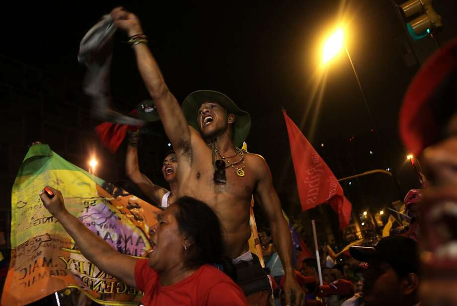 Supporters of Venezuela's President Hugo Chavez celebrate at the Miraflores presidential palace late Sunday Oct. 7, 2012. Chavez won re-election and a new endorsement of his socialist project Sunday, surviving his closest race yet after a bitter campaign against opposition candidate Henrique Capriles.(AP Photo/Rodrigo Abd) Photo: Rodrigo Abd, Associated Press