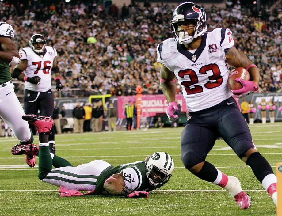Houston Texans running back Arian Foster (23) rushes for a touchdown as New York Jets strong safety Yeremiah Bell (37) falls down on the play during the first half of an NFL football game, Monday, Oct. 8, 2012, in East Rutherford, N.J. (AP Photo/Kathy Willens) Photo: Kathy Willens, Associated Press / AP