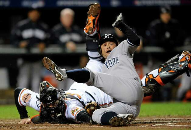 New York Yankees' Ichiro Suzuki, right, of Japan, leaps past Baltimore Orioles catcher Matt Wieters to score a run on a double by Robinson Cano in the first inning of Game 2 of the American League division baseball series on Monday, Oct. 8, 2012, in Baltimore. (AP Photo/Nick Wass) Photo: Nick Wass