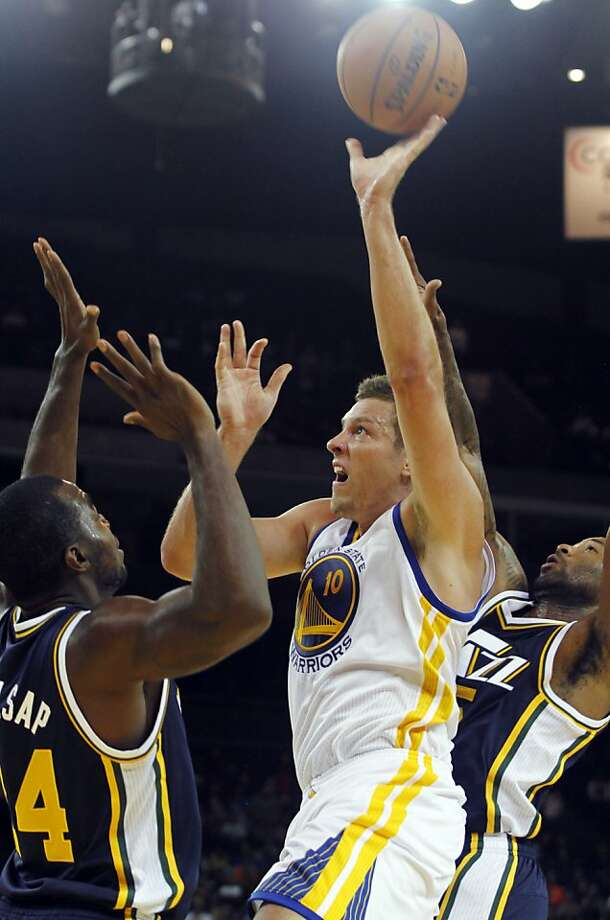 David Lee, center in photo at top, had 19 points and 14 rebounds as the Warriors improved to 2-0 in exhibition play. Left, the Warriors' Klay Thompson struggles for the ball with Utah's Paul Millsap. Photo: George Nikitin, Associated Press