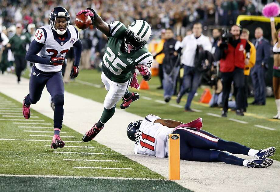 New York Jets running back Joe McKnight (25) dives into the end zone for a touchdown as Houston Texans' DeVier Posey (11) and Troy Nolan (33) trail during the second half of an NFL football game, Monday, Oct. 8, 2012, in East Rutherford, N.J. The Texans won 23-17. (AP Photo/Julio Cortez) Photo: Julio Cortez, Associated Press