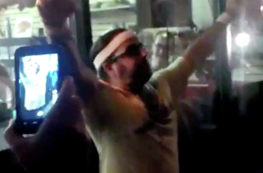 In this frame grab made from video on Friday, Oct. 5, 2012, and provided by John-Patrick McNown, Edward Archbold celebrates winning a roach-eating contest at Ben Siegel Reptile Store in Deerfield Beach, Fla. Archbold, 32, died shortly after downing dozens of the live bugs as well as worms, authorities said Monday, Oct. 8. Authorities were waiting for results of an autopsy to determine a cause of death. (AP Photo/Courtesy John-Patrick McNown) Photo: John-Patrick McNown