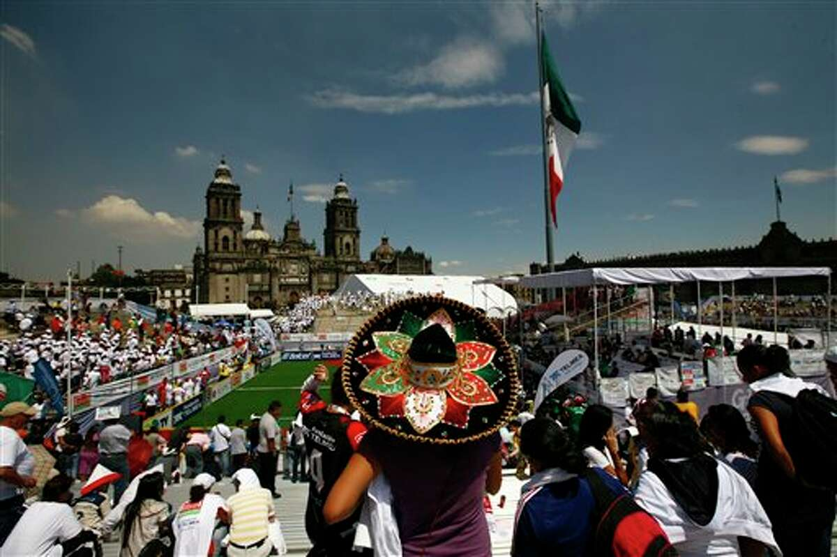 A woman wearing a decorative Mexican sombrero watches the Homeless World Cup soccer tournament in Mexico City's Zocalo plaza, Saturday Oct. 6, 2012. The Homeless World Cup organization puts together the yearly championship in cities worldwide since 2003, using soccer as a means to help homeless people change their lives. (AP Photo/Marco Ugarte)