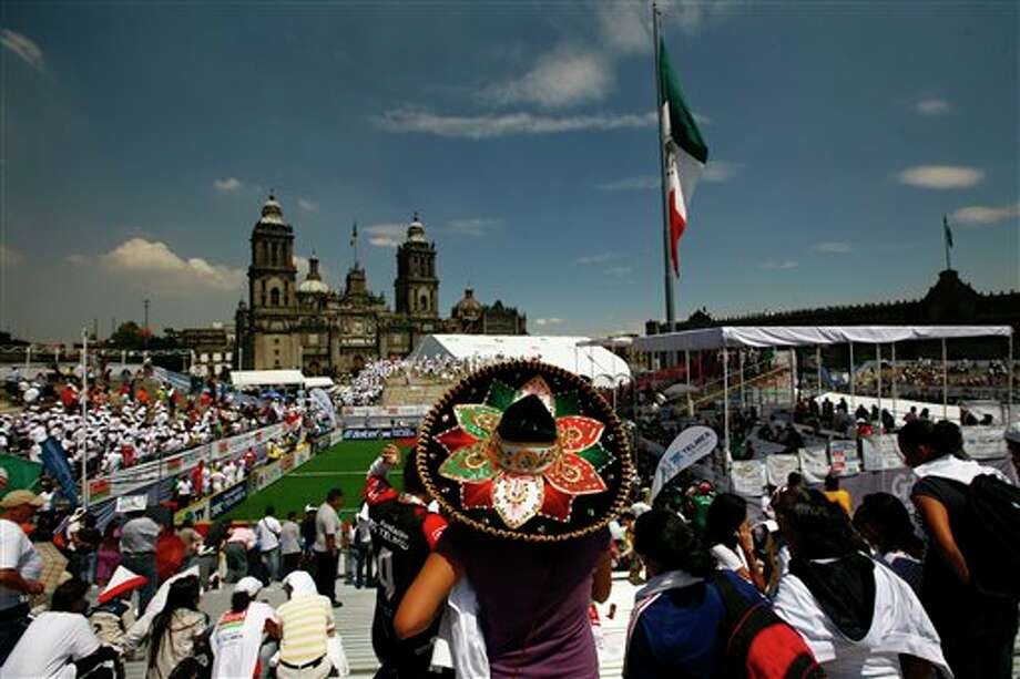 A woman wearing a decorative Mexican sombrero watches the Homeless World Cup soccer tournament in Mexico City's Zocalo plaza, Saturday Oct. 6, 2012. The Homeless World Cup organization puts together the yearly championship in cities worldwide since 2003, using soccer as a means to help homeless people change their lives. (AP Photo/Marco Ugarte) Photo: Marco Ugarte, AP / AP