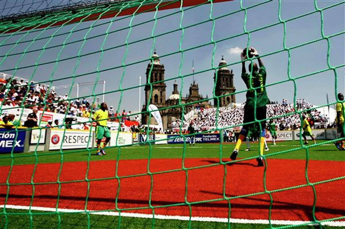 The goal keeper for team South Africa blocks a shot by team Mexico during the Homeless World Cup soccer tournament in Mexico City's Zocalo plaza, Saturday, Oct. 6, 2012. The Homeless World Cup organization puts together the yearly championship in cities worldwide since 2003, using soccer as a means to help homeless people change their lives. (AP Photo/Marco Ugarte)