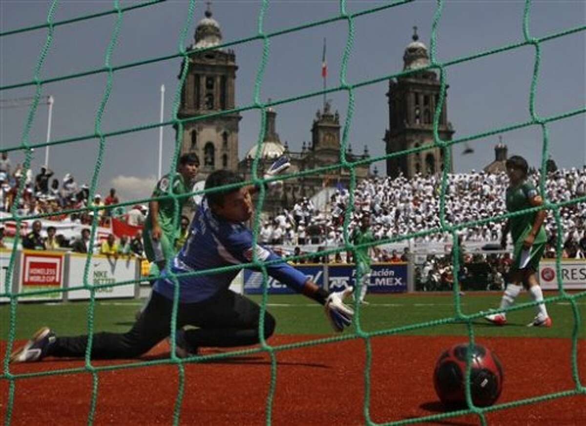 Mexico's goal keeper fails to stop a goal by South Africa during the 2012 Homeless World Cup soccer tournament in Mexico City's Zocalo plaza, Saturday, Oct. 6, 2012. Since 2003 the annual competition has been hosted by cities across the world as homeless players unite to celebrate changing their lives and raise awareness of homelessness. (AP Photo/Marco Ugarte) (AP)